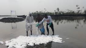 Eine stark verunreinigte Gegend im Tidenbereich des Nigers wird mit PURE gereinigt. Dabei bindet das Ölbindemittel das Öl von der Wasseroberfläche.
